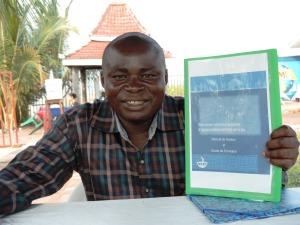 Jean Claude Kalundu, avec le Manuel de gestion et guide de formation des comités de gestion d'eau du Consortium WASH RDC